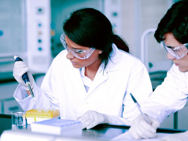 students with pipette and test samples in lab