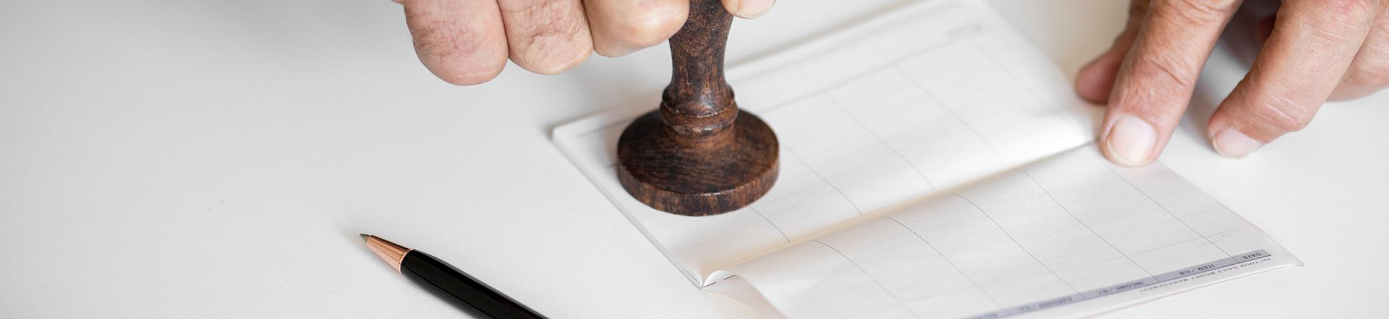 male hands stamping a checkbook